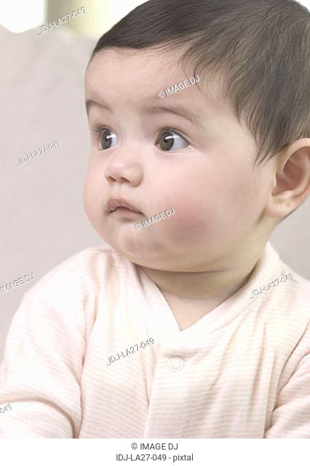 Close-up of a baby girl looking sideways
