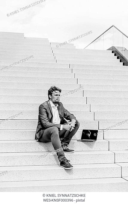 Businessman sitting on stairs with laptop