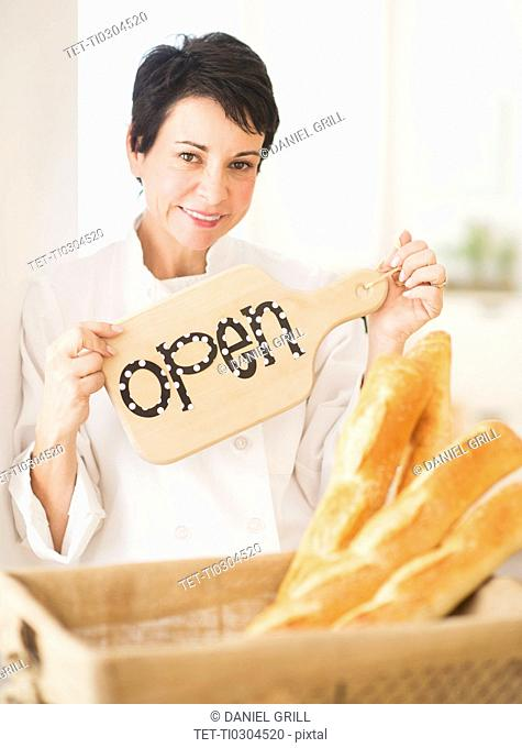 Portrait of mature woman holding basket with baguettes