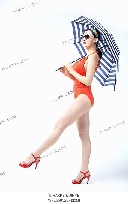 Side view of young woman in swimsuit walking holding umbrella