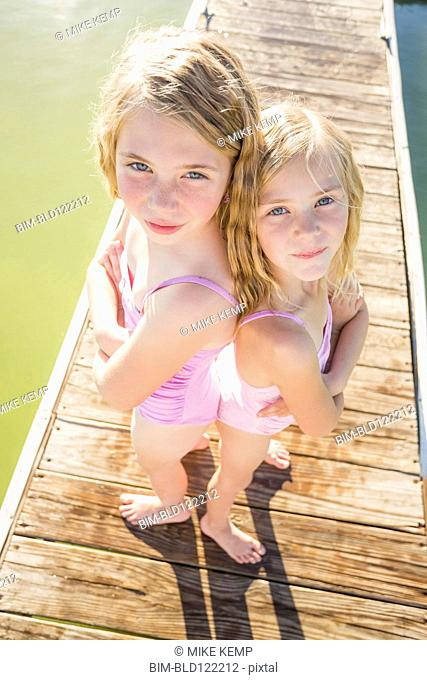 Caucasian girls standing back to back on dock