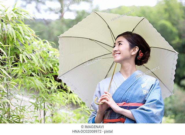 Young Japanese woman in kimono with parasol