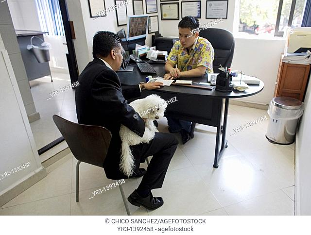 A man holds his dog as he speaks with a veterinarian at a Pet Hospital in Condesa, Mexico City, Mexico, February 9, 2011