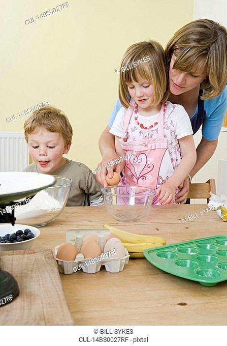 boy, girl and mum making fruit muffins