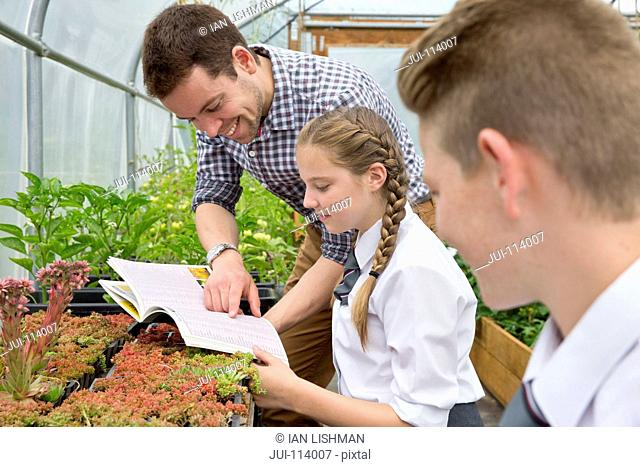 Teacher and middle school students with book learning gardening in plant greenhouse