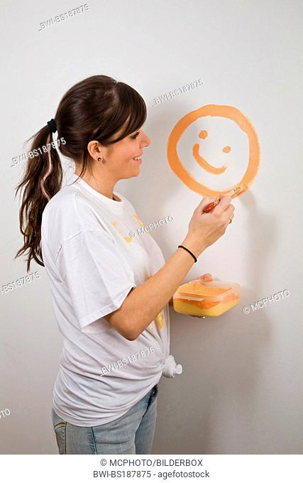 Young woman paints smilies on a wall