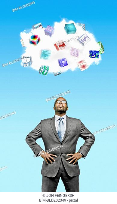 African American businessman looking at cloud containing cubes with pictures