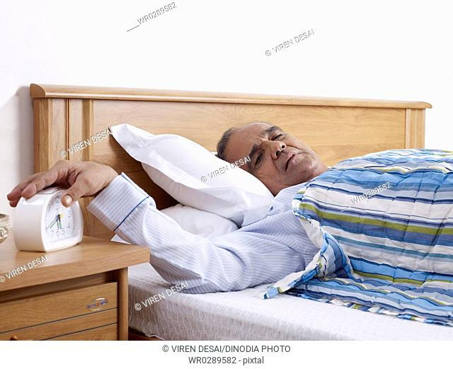 Old man reclining on bed hand stopping ringing alarm clock MR702T