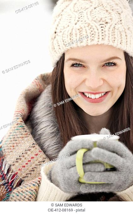 Close up portrait of woman in knit hat and gloves drinking coffee