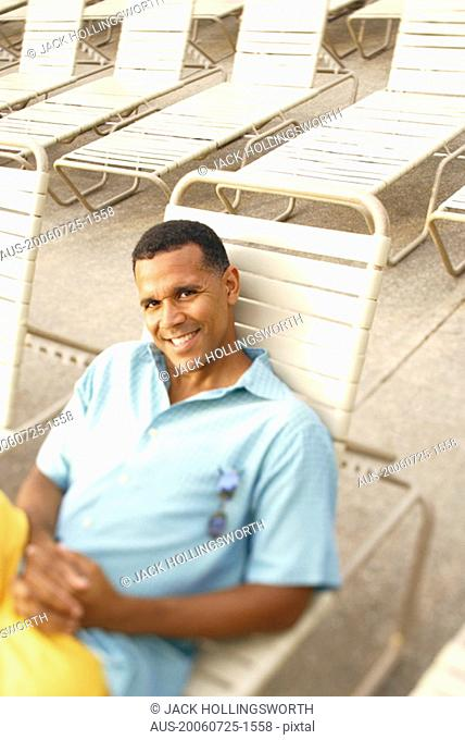 High angle view of a mature man reclining on a lounge chair