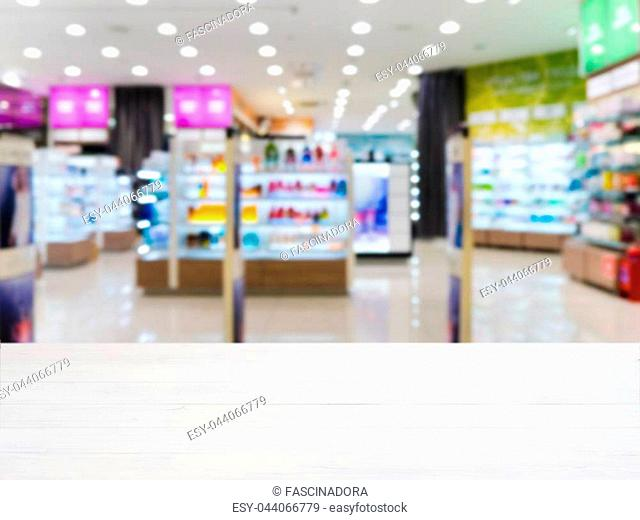 White wooden board empty table in front of blurred background. Perspective white wood over blur in supermarket - can be used for display or montage your...