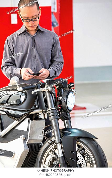 Technician in garage, checking electric cafe racer motorbike on smartphone