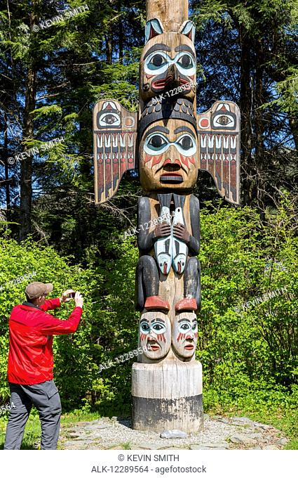 Tourist photographs a totem pole, Totem Bight Historic State Park, Ketchikan, Southeast Alaska, USA, Spring