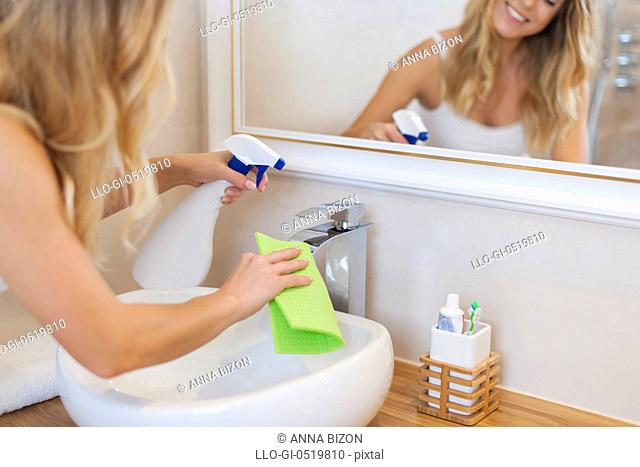 Blonde young woman cleaning bathroom. Debica, Poland