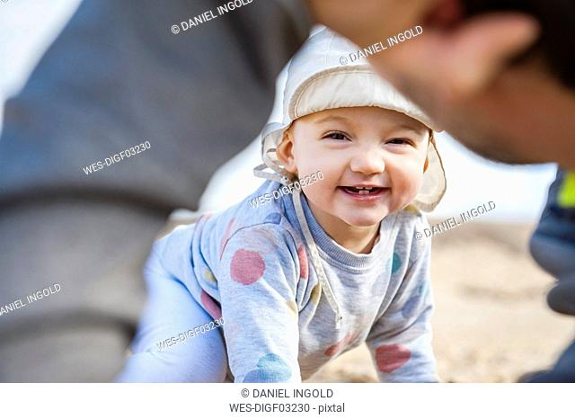 Spain, Lanzarote, portrait of laughing baby girl playing with father on the beach
