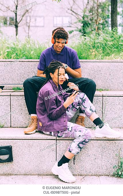 Brother and sister watching footage on mobile phone together, Milan, Italy