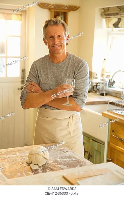 Portrait smiling senior man drinking wine and baking in kitchen