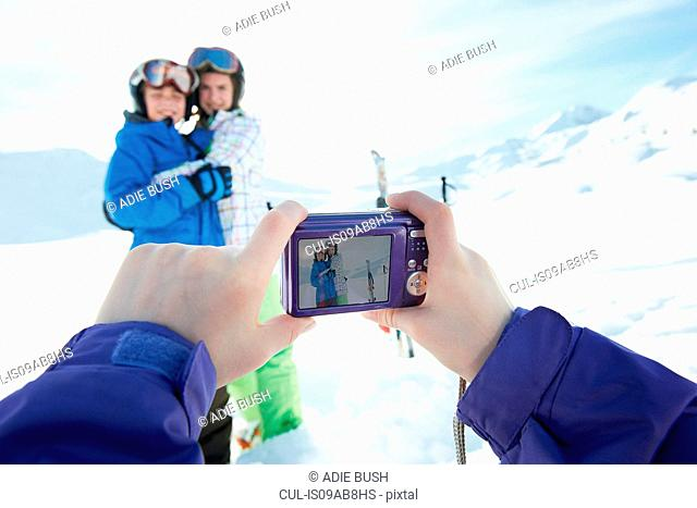 Sister photographing siblings in snow, Les Arcs, Haute-Savoie, France