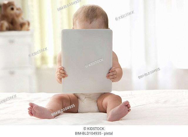 Hispanic baby using digital tablet