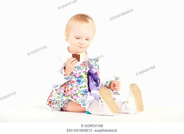 Little girl in a colorful dress with cookies and glass in hand