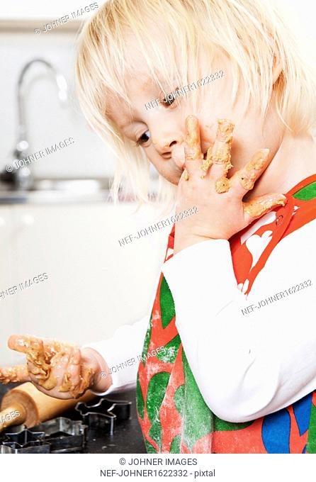 Boy licking fingers while doing gingerbread