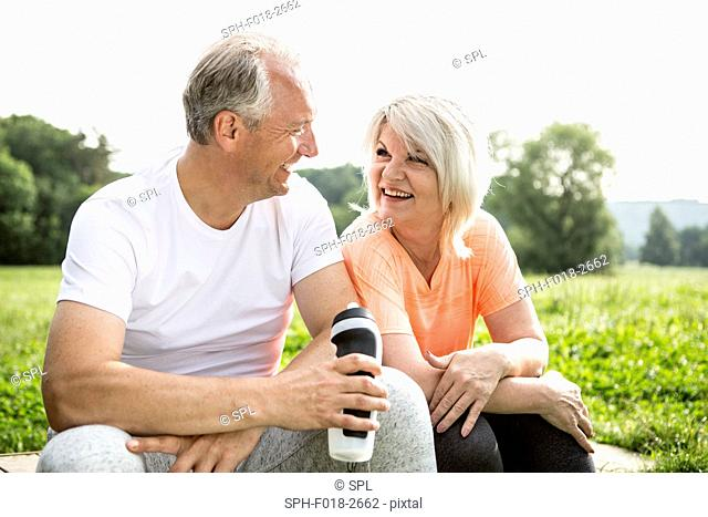 MODEL RELEASED. Mature couple sitting outdoors resting, man holding water bottle