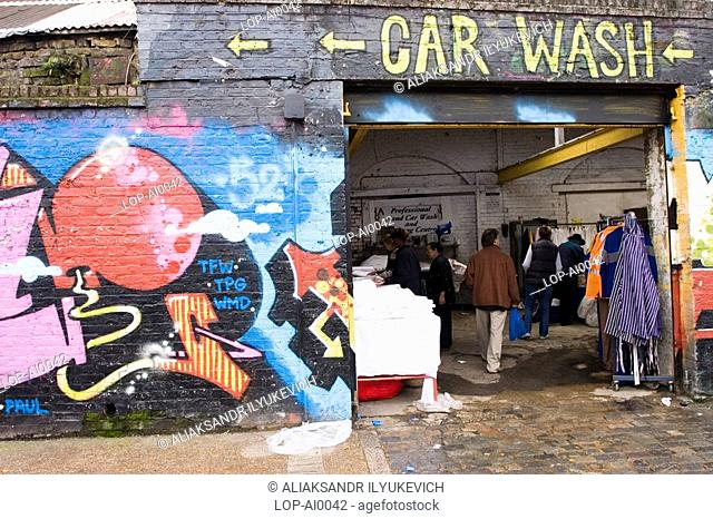 England, London, London, East End Market with graffiti. The word 'graffiti' is the plural of 'graffito' and originates from the Italian word 'graffiato' which...
