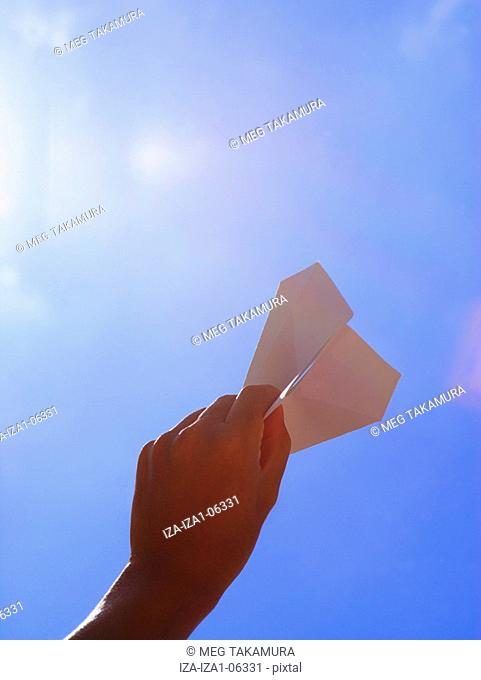Low angle view of a person's hand holding a paper airplane