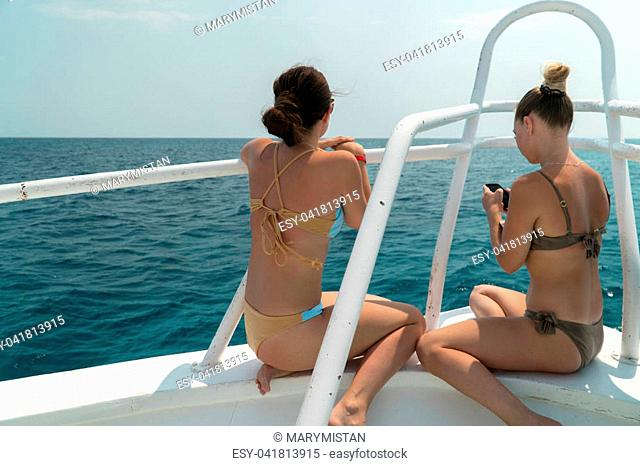 Girls in bathing suits sit at the side of the yacht and enjoy the view