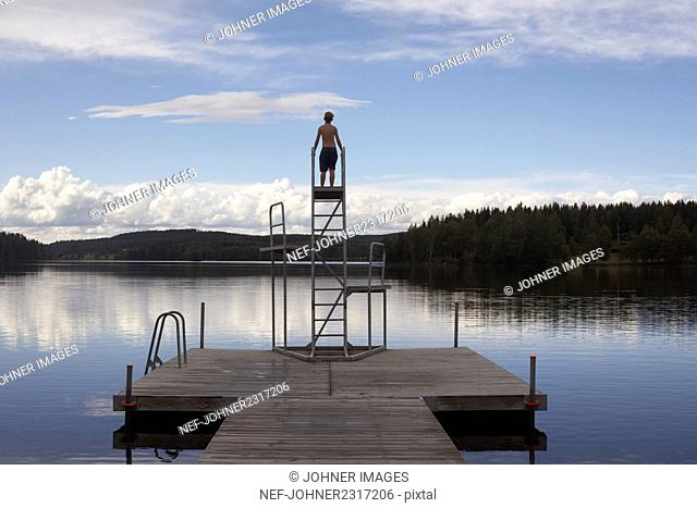 Boy standing on top of jumping tower at lake