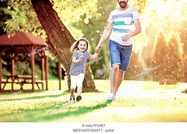 Portrait of smiling little girl running with her father hand in hand in a park
