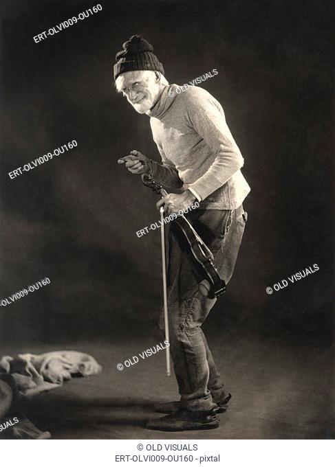 Senior man in woolen cap holding a violin