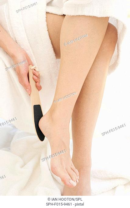 MODEL RELEASED. Young woman using pedicure equipment