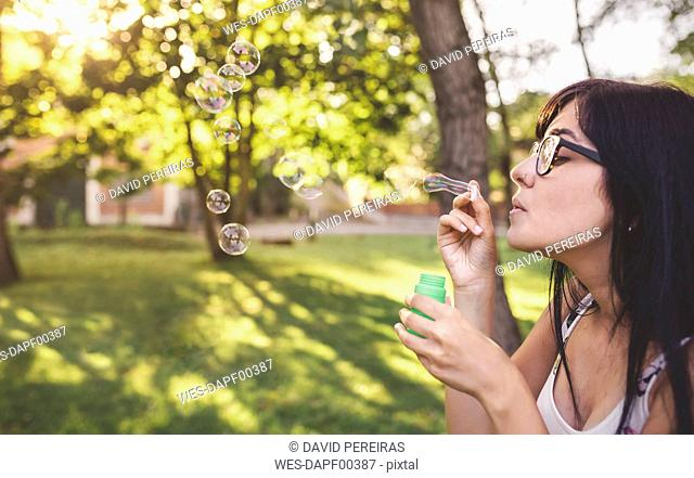 Young woman blowing soap bubbles in park