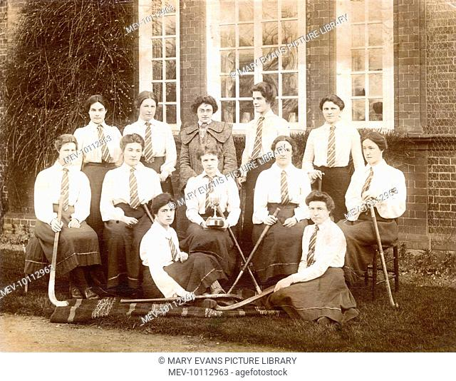 A photograph of the Newnham College, Cambridge ladies hockey team; the captain sits in the centre with a trophy
