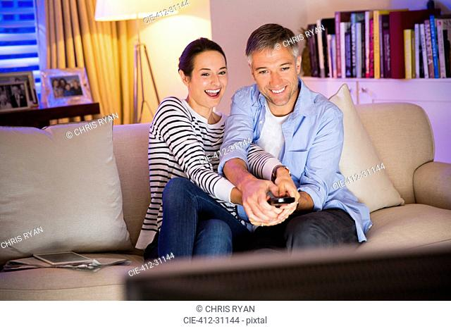 Playful couple fighting over remote control watching TV in living room
