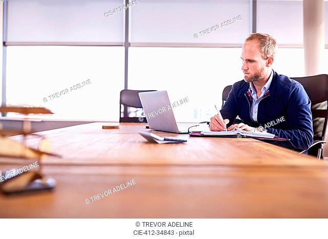 Focused businessman taking notes at laptop in conference room