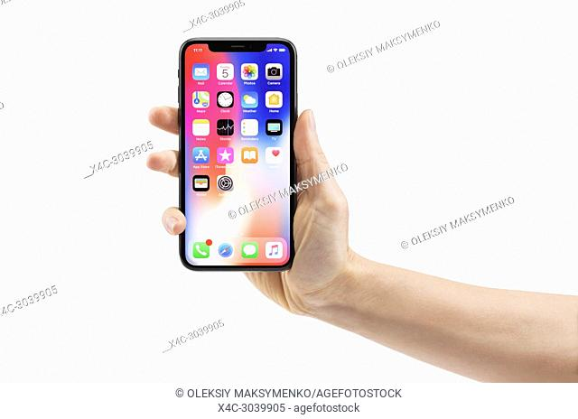 Woman hand holding Apple iPhone X, large screen smartphone, with colorful blue red desktop on its display. The phone is isolated on white background with a...
