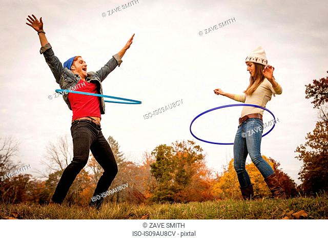 Young couple playing with plastic hoops in autumn park