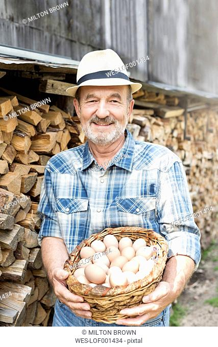 Smiling farmer on organic farm holding basket with eggs