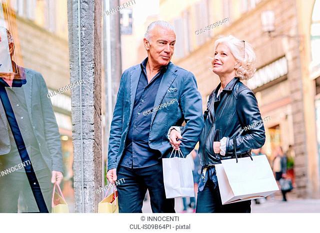 Tourist couple window shopping on city street, Siena, Tuscany, Italy