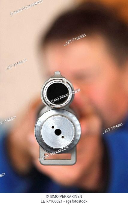 A man takes aim with a pump action shotgun