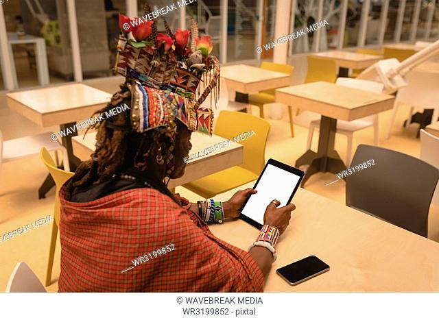 Maasai man in traditional clothing using digital tablet