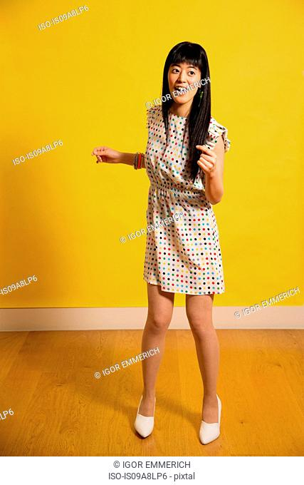 Portrait of young woman wearing spotted dress dancing