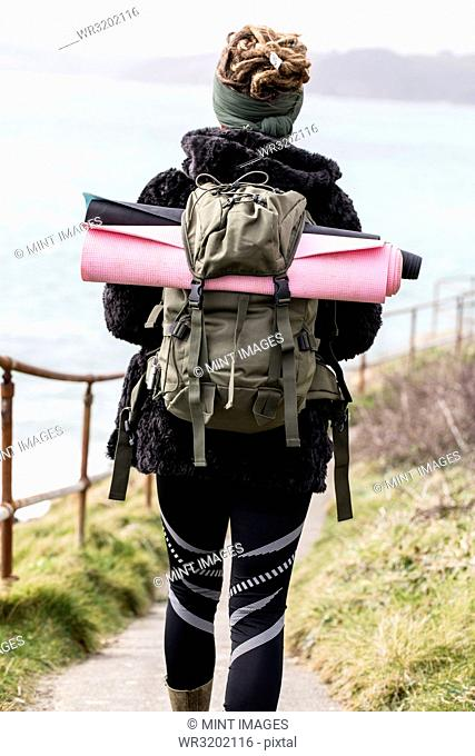 Rear view of young woman with brown hair and dreadlocks carrying backpack, walking along coastal hiking path