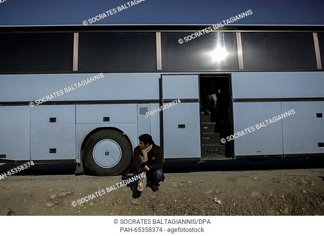 A migrant sits outside of a bus as he waits to cross the Greek-Macedonian border at Idomeni village, Greece, 25 January 2016