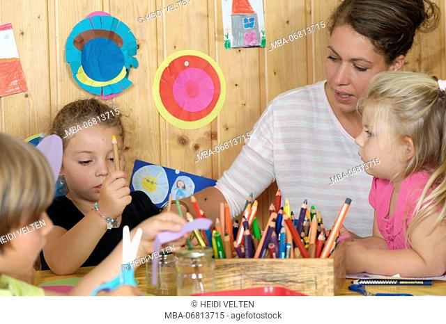 Children and childcare assistant doing handicrafts, half portrait