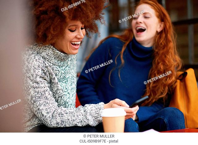Friends at coffee shop using mobile phone laughing