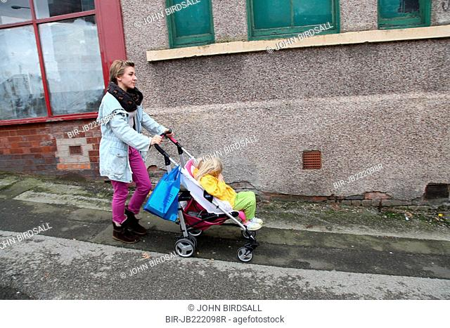 Mother out walking with toddler in buggy