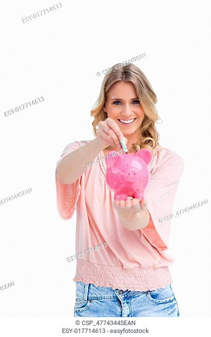 Smiling woman putting money in a piggy bank that she is holding